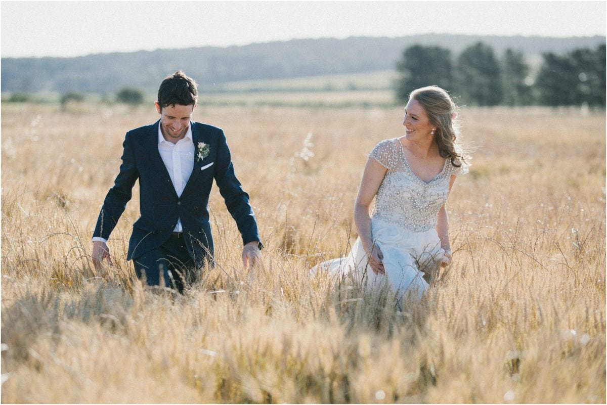 A newly married couple walk through a field of wheat after their Aghadoe Estate wedding