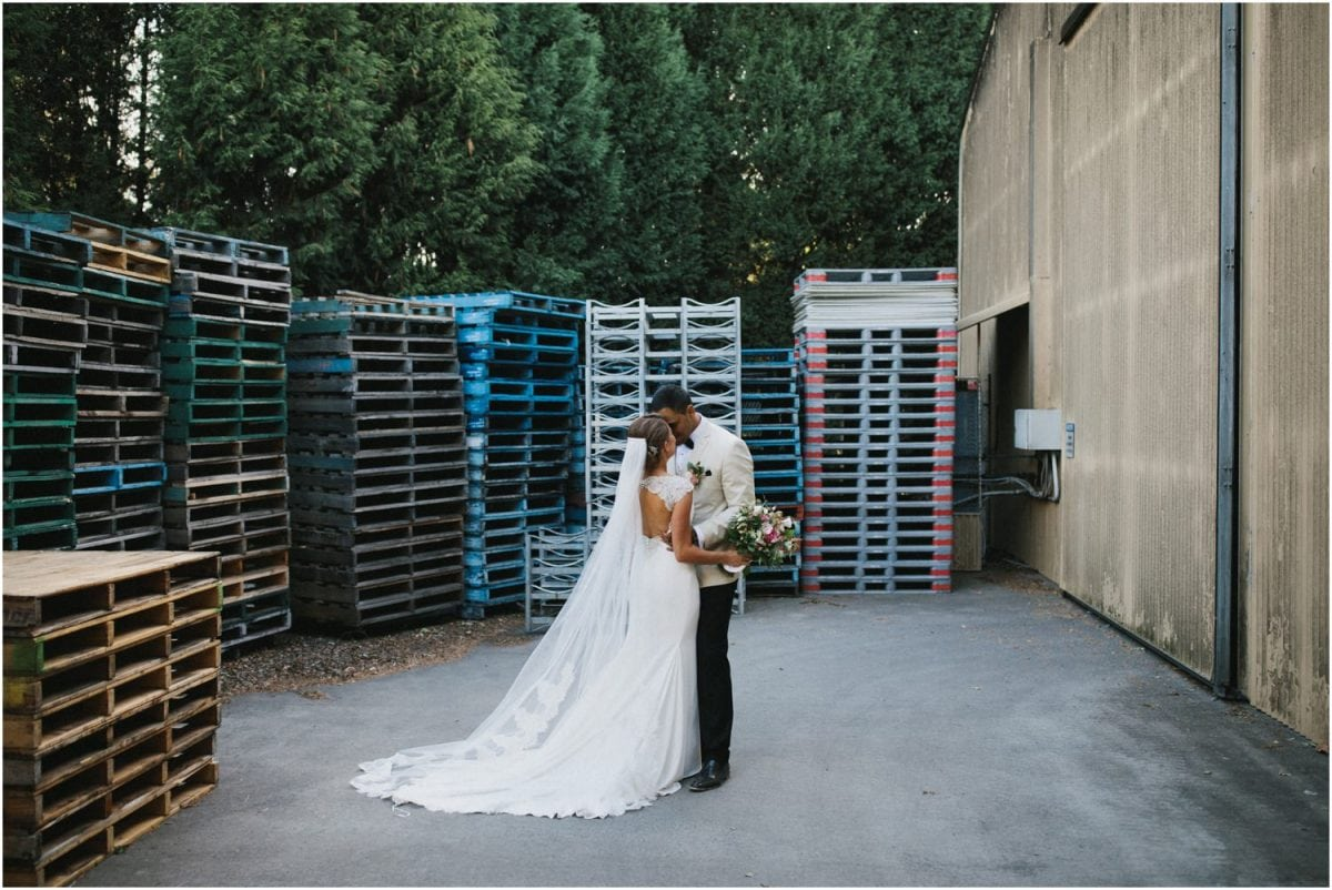 A bride and groom pose for a photo near some wine pallets after their Centennial Vineyards Bowral wedding