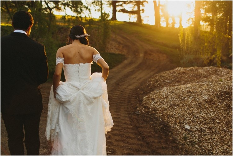 A newly married couple walk along a dirt road into the sunset after getting married at their Peppers Manor House wedding. The bride is in a lovely white dress.