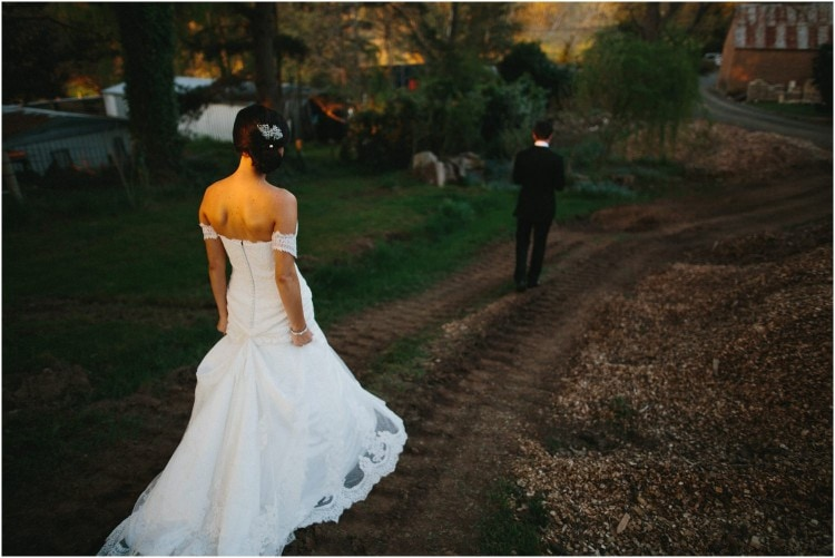 After their Peppers Manor House wedding, a bride and groom stroll around the lovely grounds of the venue. The groom walks ahead of the bride. You can see the back of the bride's dress.