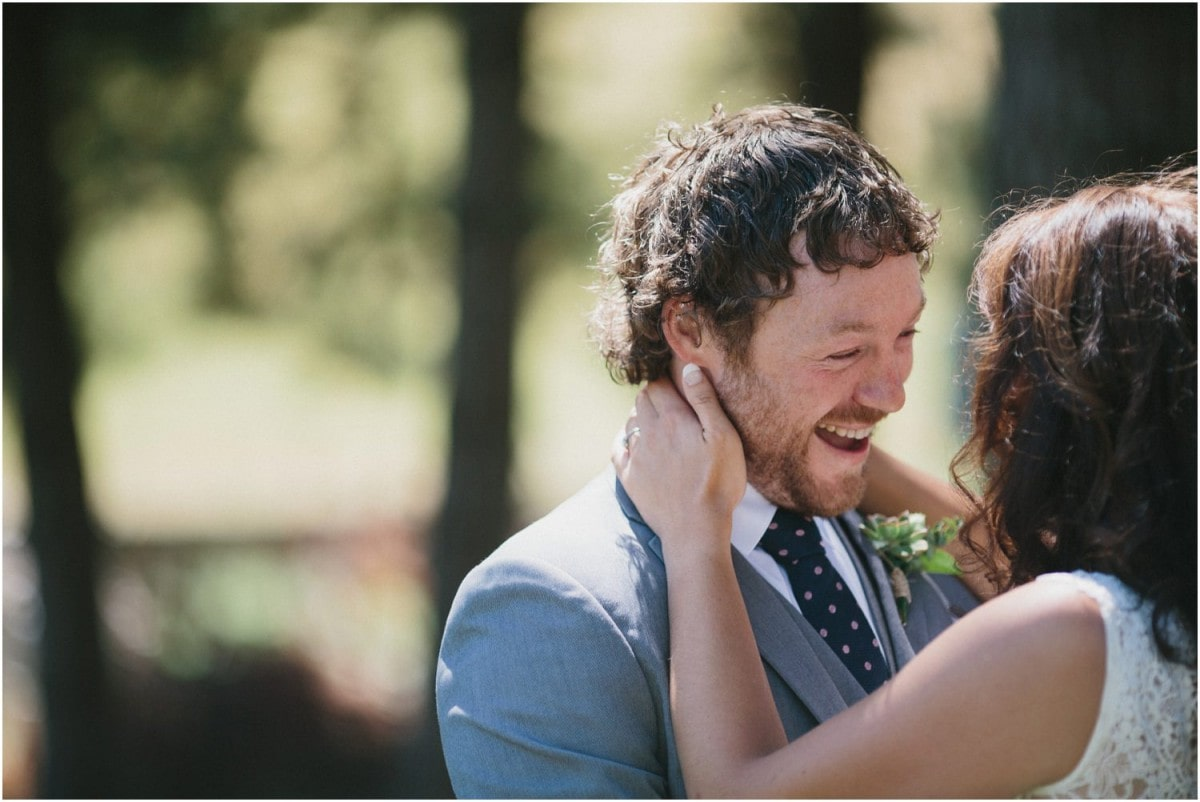 A groom laughs while talking with his bride at their New Zealand wedding