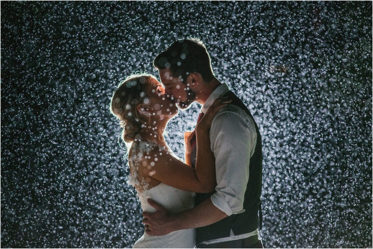 A couple kiss late at night in the rain, taken by their Southern Highlands photographer