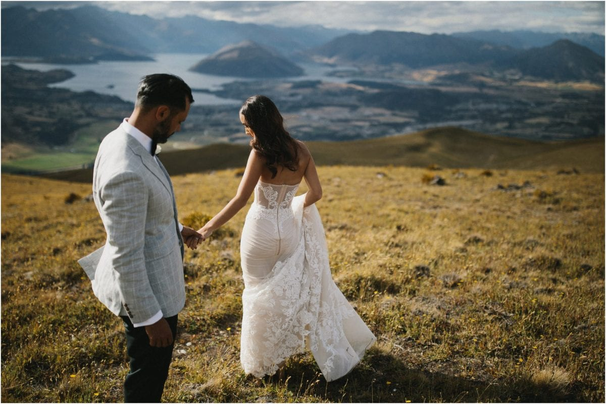 A bride and groom stand atop a mountain after their Wanaka wedding