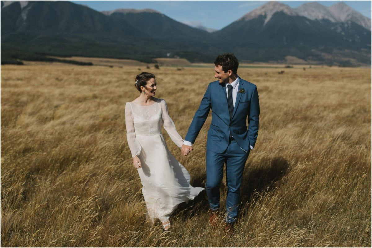 A bride and groom walk through a field of long grass after their Arthur's Pass wedding