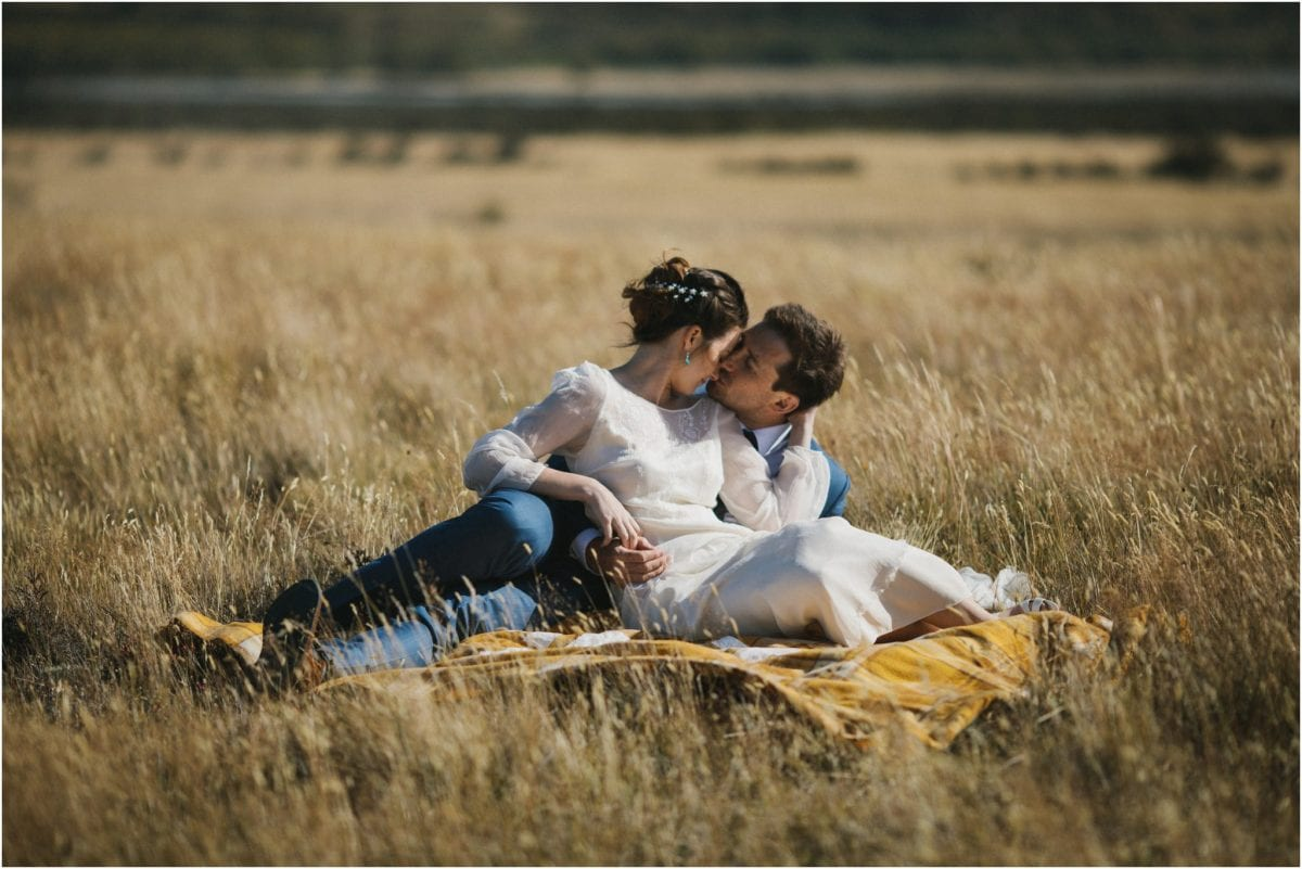 A couple sit in long grass after their Arthur's Pass wedding in New Zealand