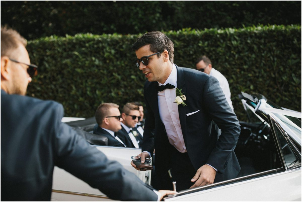 Groom gets out of old Cadillac at his Bendooley Berrima wedding