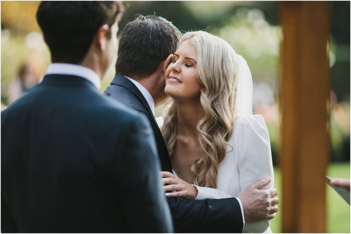 Bride's father kisses her cheek at her Bendooley Berrima Wedding