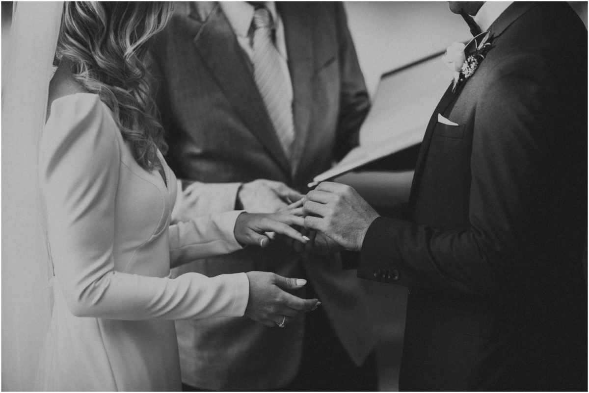 Bride and groom exchange rings during their wedding ceremony