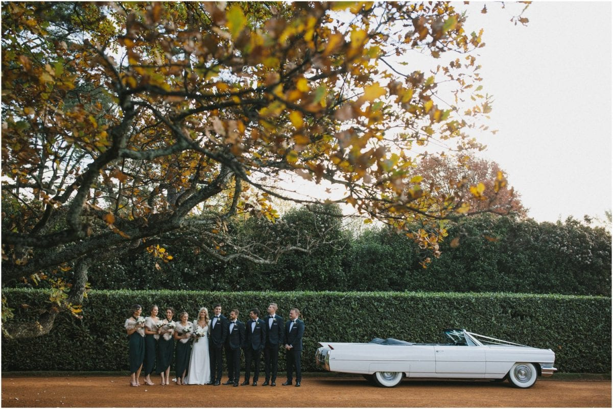 Bridal party pose next to a Cadillac at Bendooley Estate
