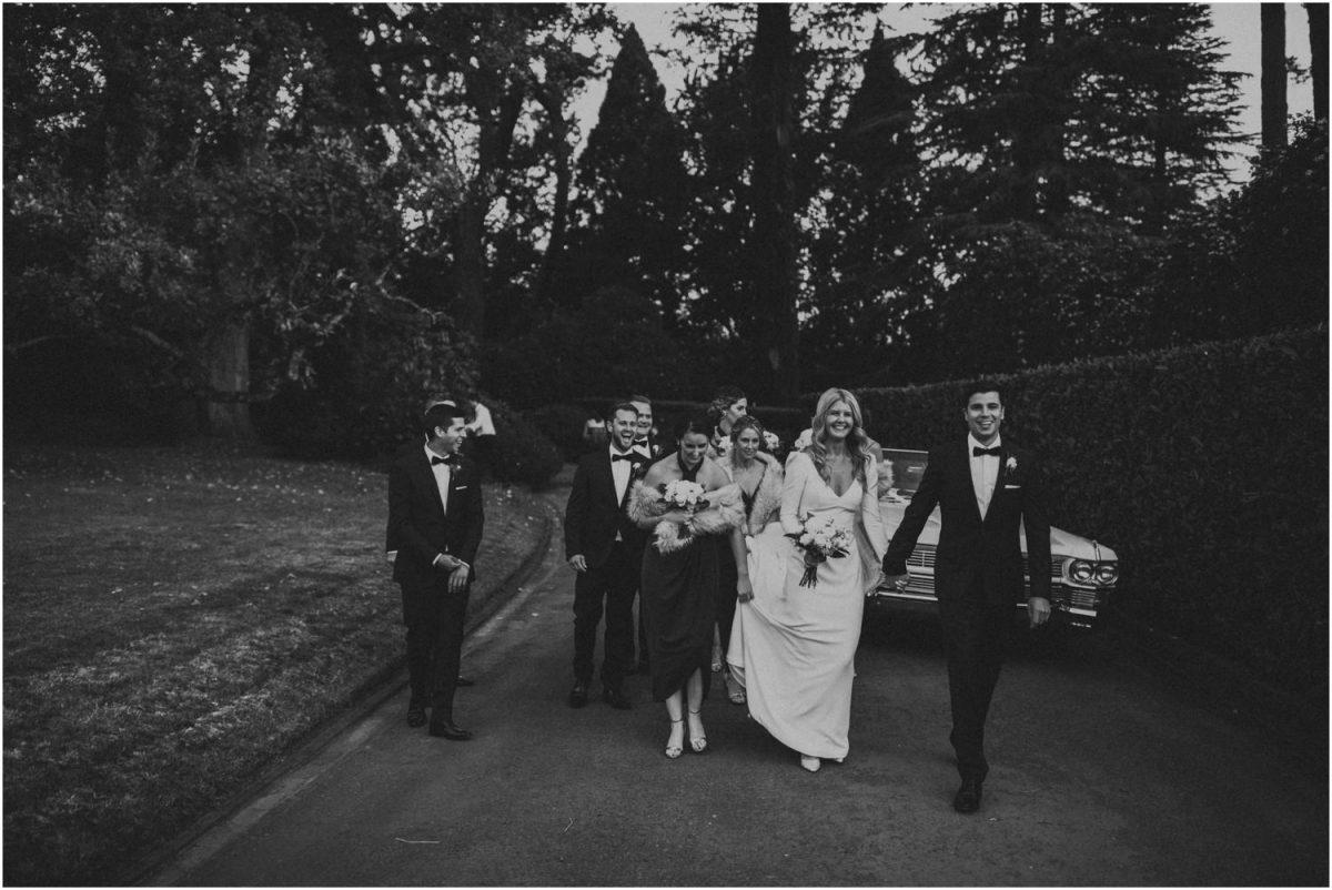 Bridal party walking near Cadillac