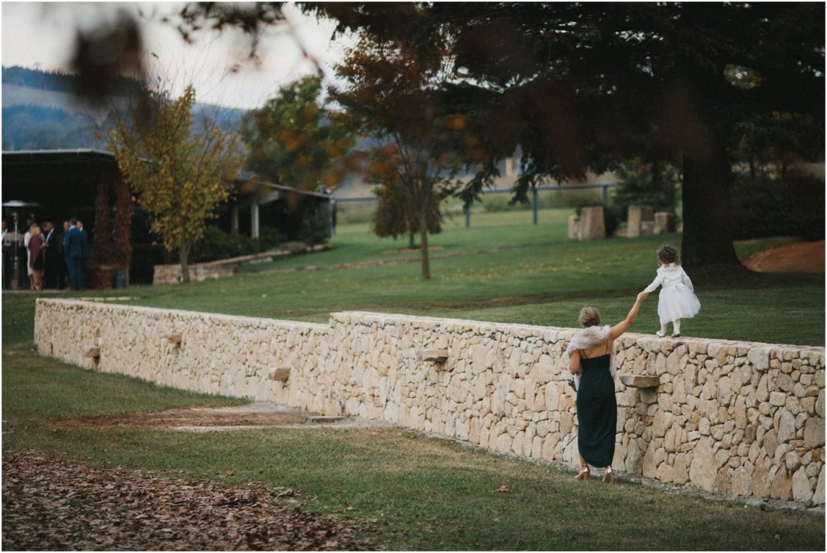 A child walks hand in hand with her mother along a stone wall