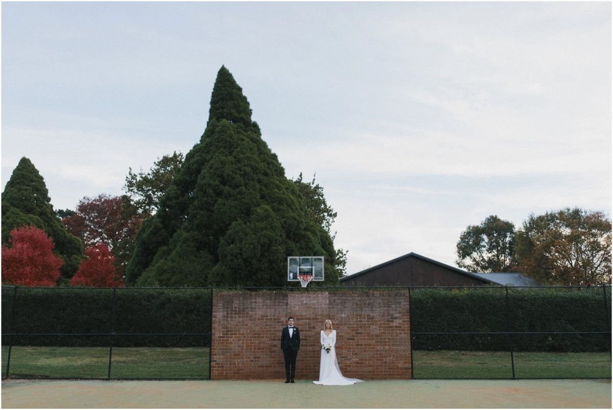 Bride and groom at Bendooley Estate in front of a basketball hoop