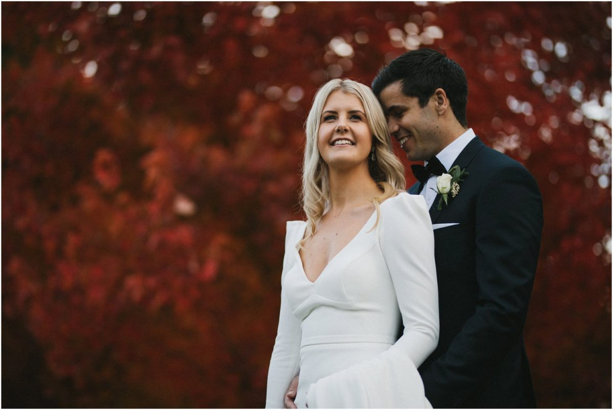 Bride and groom pose against autumn colours