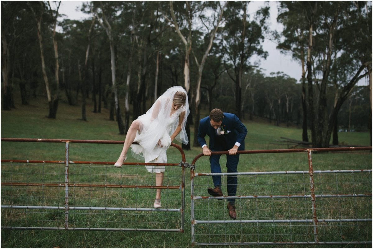 Newly married couple cimbing a fence in this photo taken by me, a Bowral Photographer