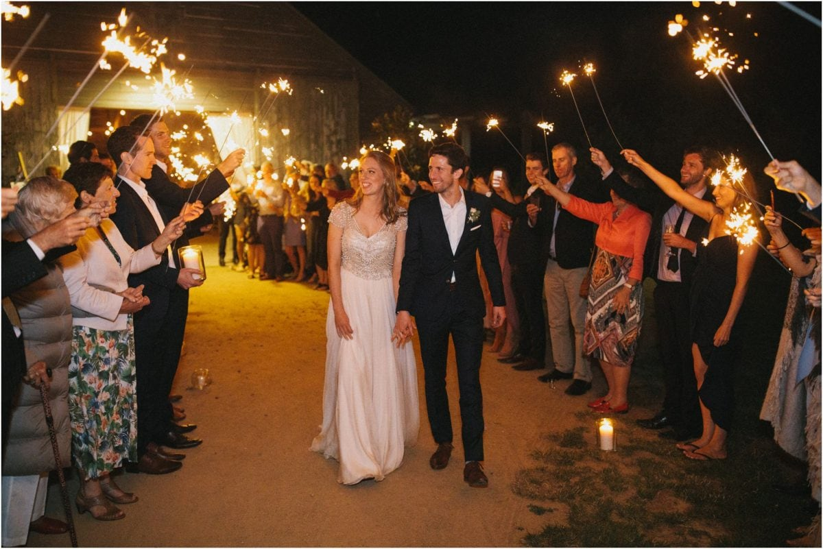 A bride and groom walk through an aisle of sparklers at the end of their Aghadoe Estate wedding reception