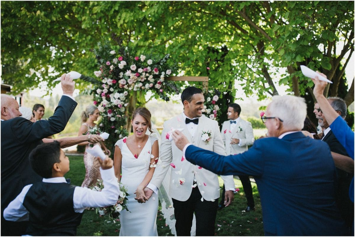 A bride and groom walk down the aisle with confetti being thrown at them at a Centennial Vineyards Bowral wedding