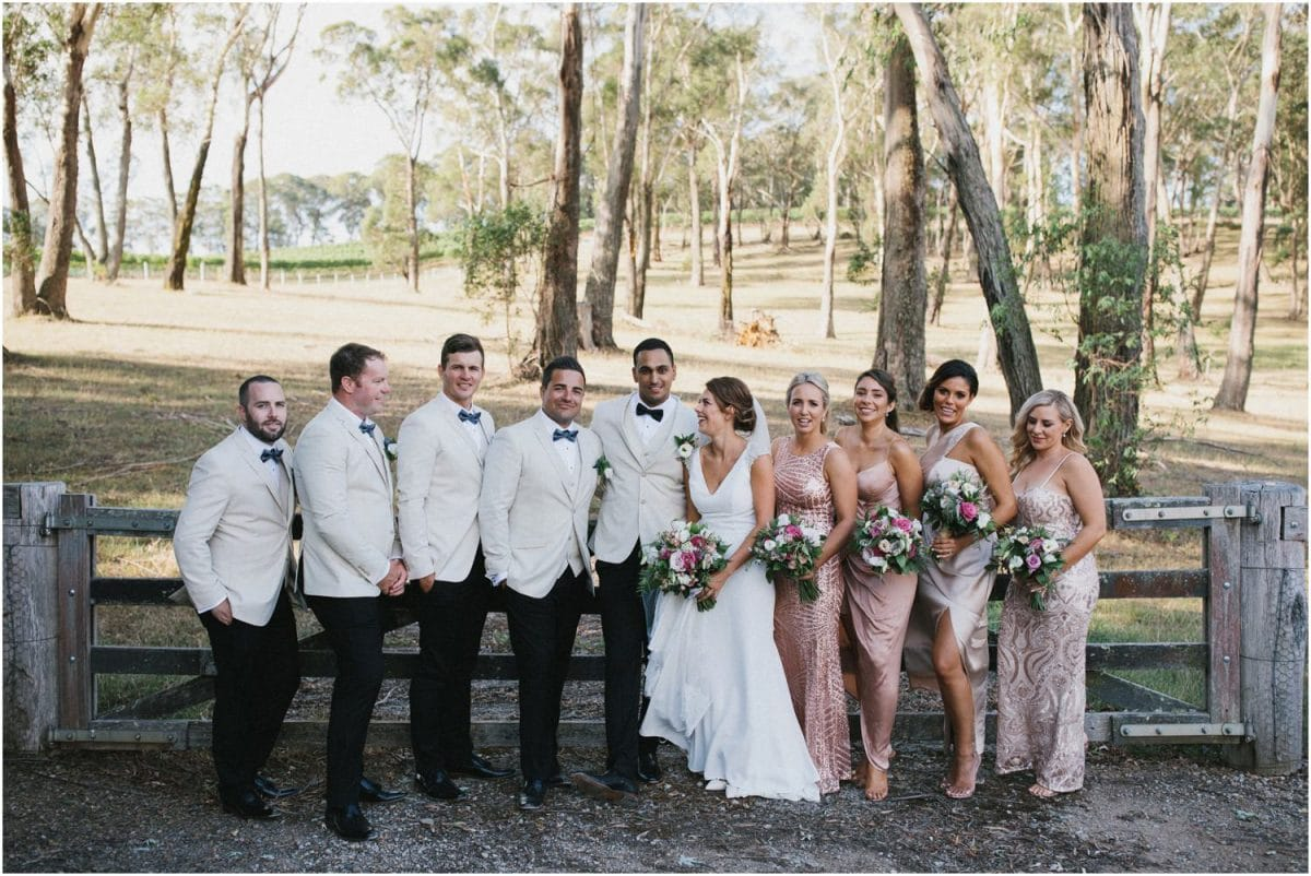 A bridal party in front of an old wooden gate at a Centennial Vineyards Bowral wedding