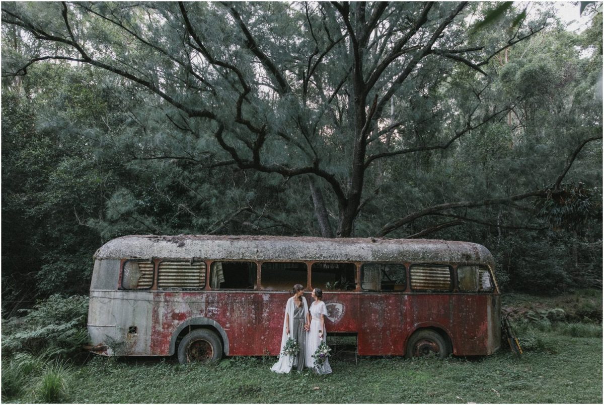 Newly married couple in front of an old abandoned bus after their kangaroo valley same sex wedding ceremony