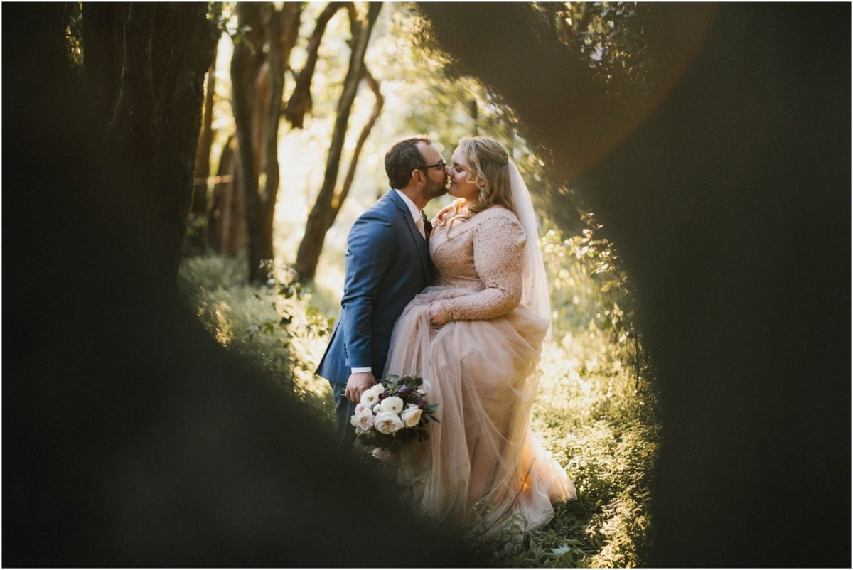 Newly married couple post in the forest after their Robertson Hotel wedding