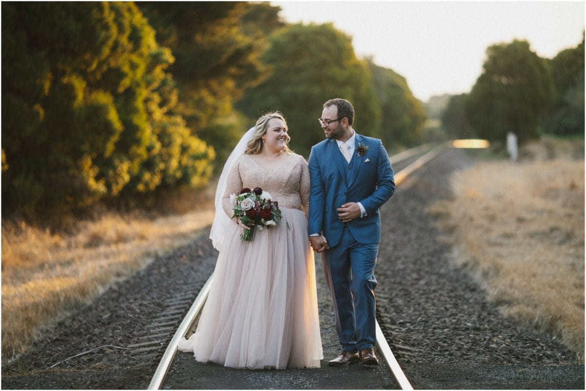 A married couple stand on train tracks after their Robertson Hotel wedding