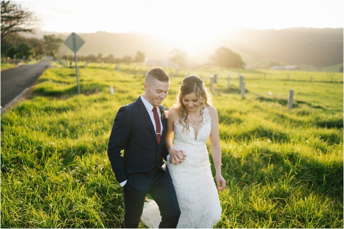 A couple walk through a field after their Mercure Gerringong wedding