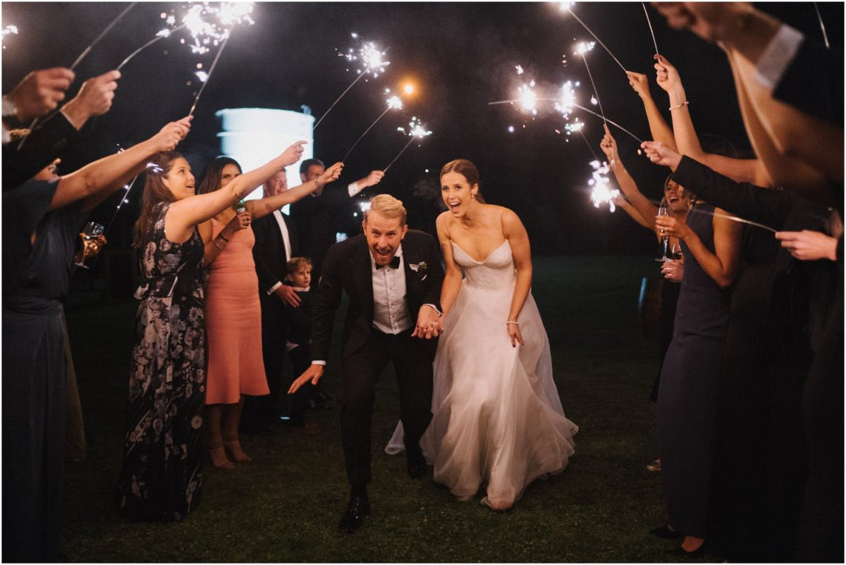 A bride and groom exit through a tunnel of sparklers held by their guests at their Melross wedding