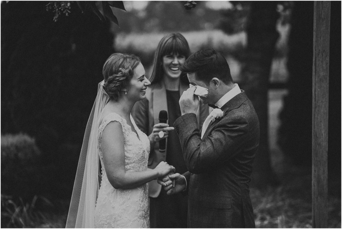 A groom wipes his eye after crying during his Centennial Vineyards wedding ceremony