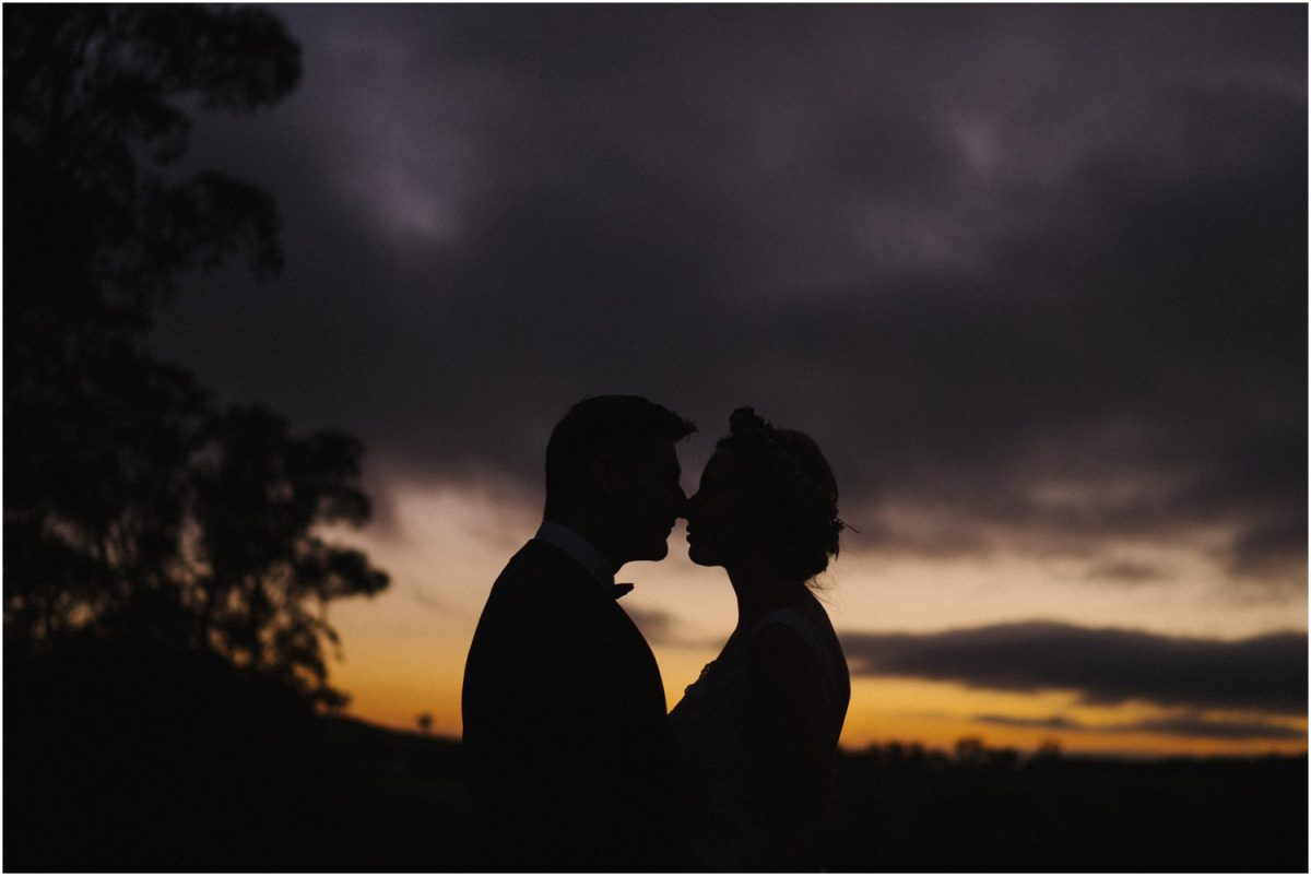 A newly married couple pose against a sunset after their Centennial Vineyards wedding