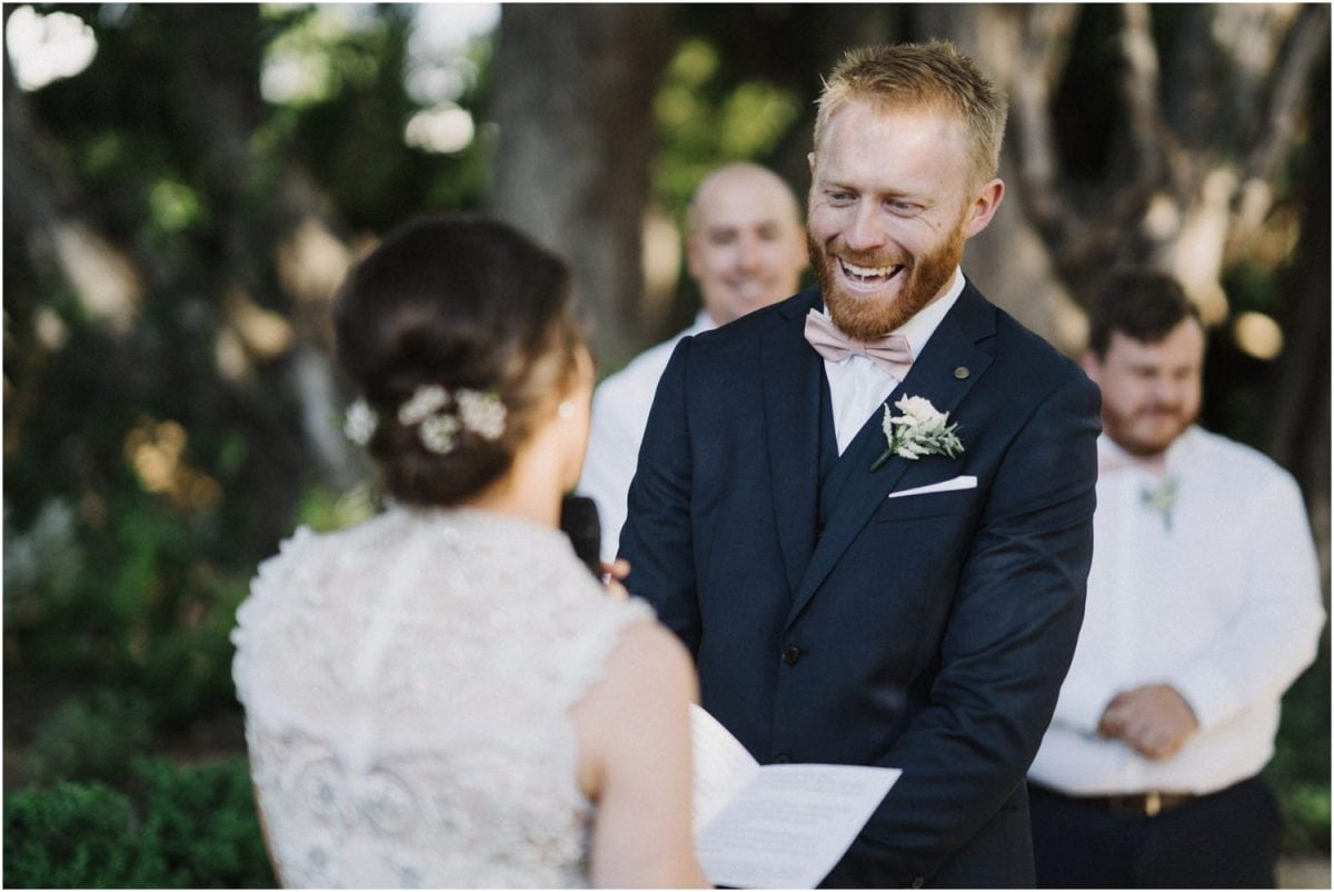 A groom laughs as he listens to his bride's vowels at their Italian Food Project wedding