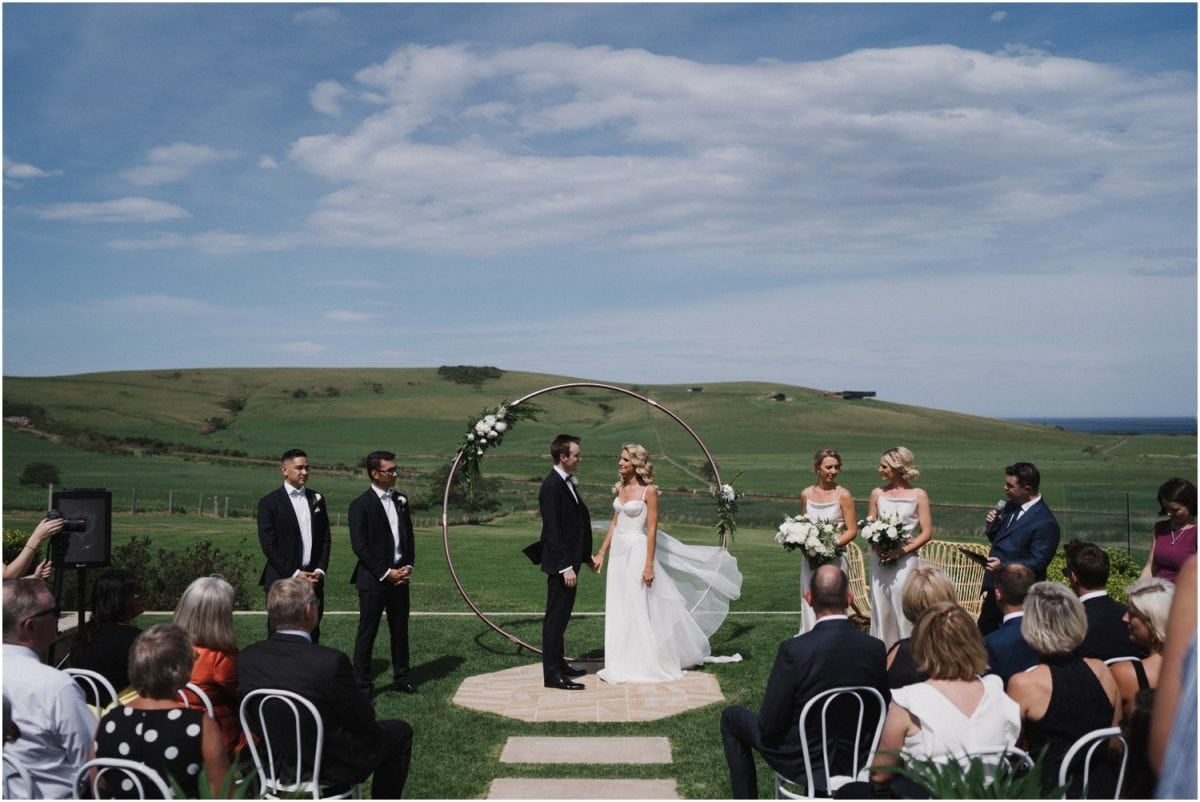 A couple stand in front of their guests at their Seacliff House wedding ceremony