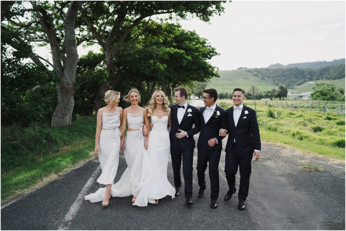 A bridal party walk down a quiet country lane at a Seacliff House wedding