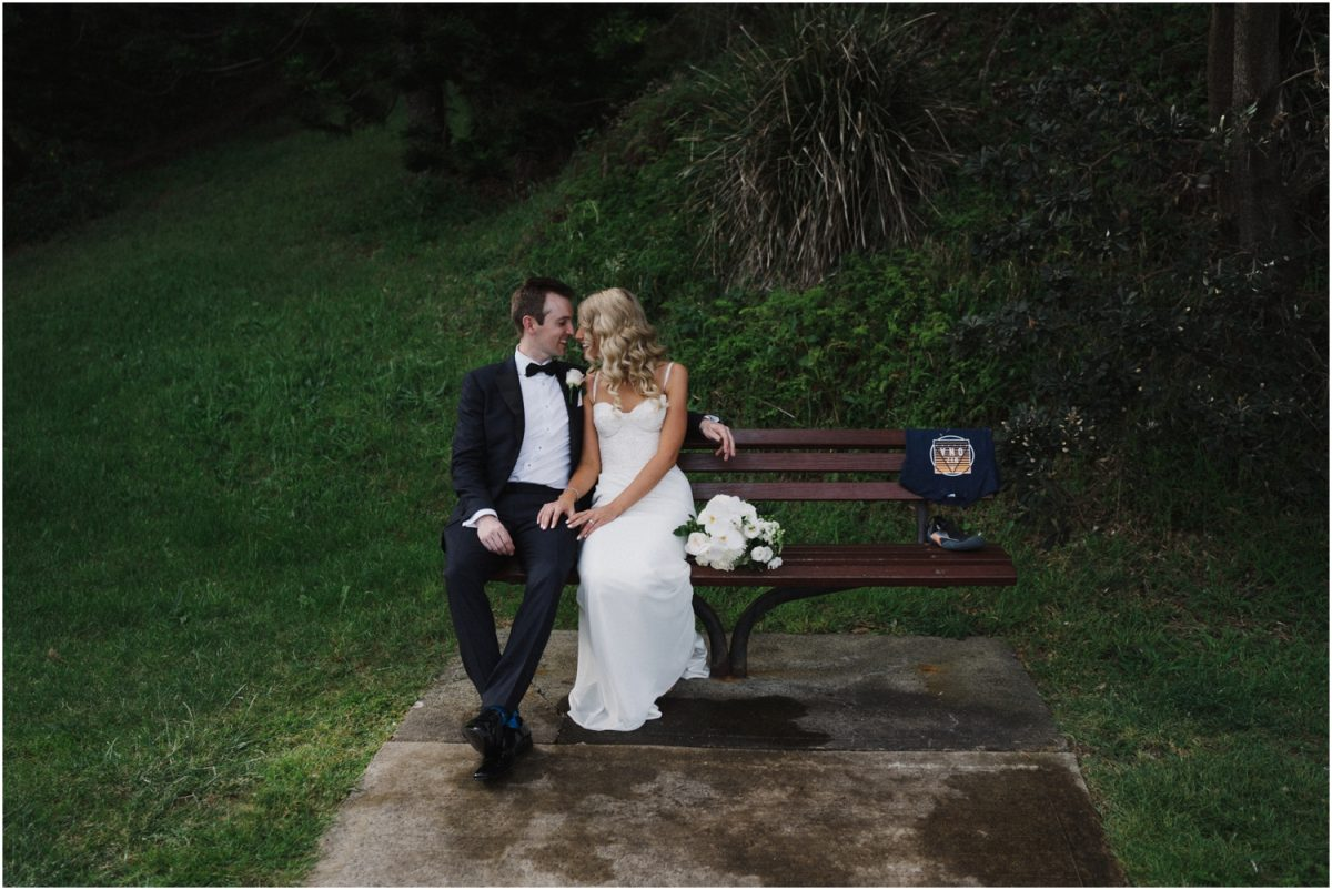 A bride and groom sit on a chair after their Seacliff House wedding