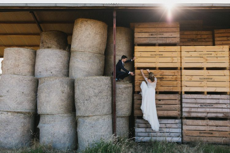 An adventurous couple in wedding attire climb some hay bails in an old shed in this photo by Southern Highlands wedding photographer Thomas Stewart