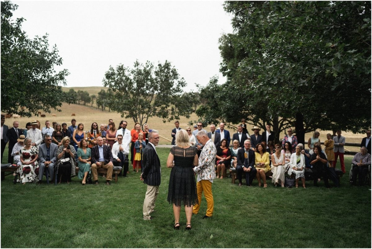 A Bendooley Stables wedding ceremony, with the celebrant and couple in the foreground, and the guests in the background