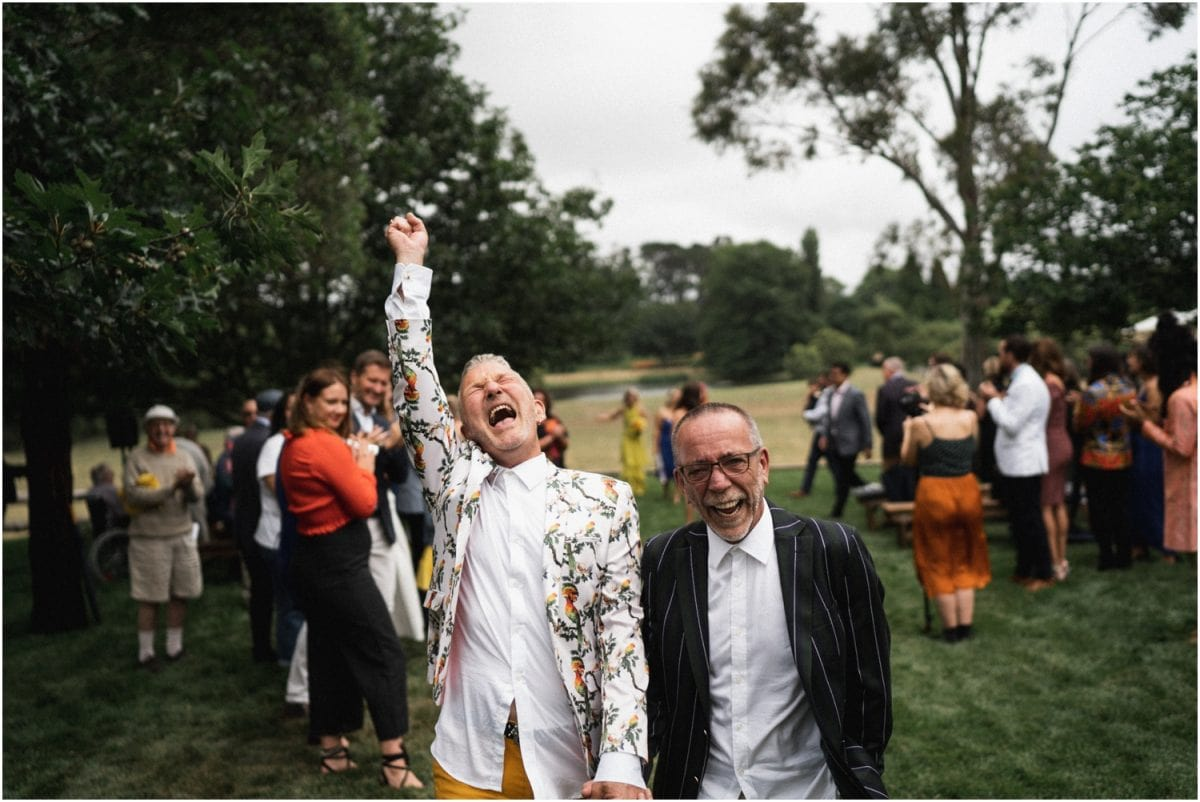 A newly married couple walk back down the aisle after their Bendooley Stables wedding; one groom is throwing his hand into the air out of apparent happiness