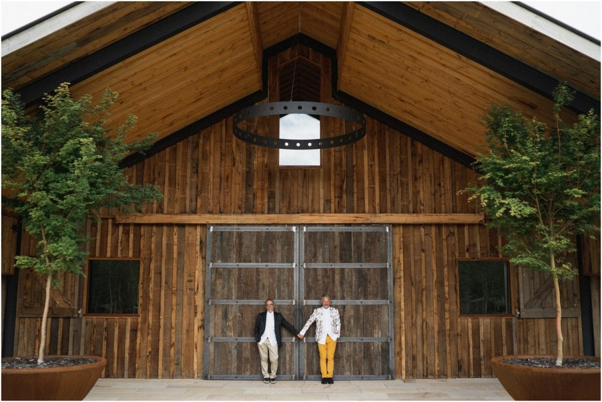 A same-sex couple stand against a huge barn door at their Bendooley Stables wedding
