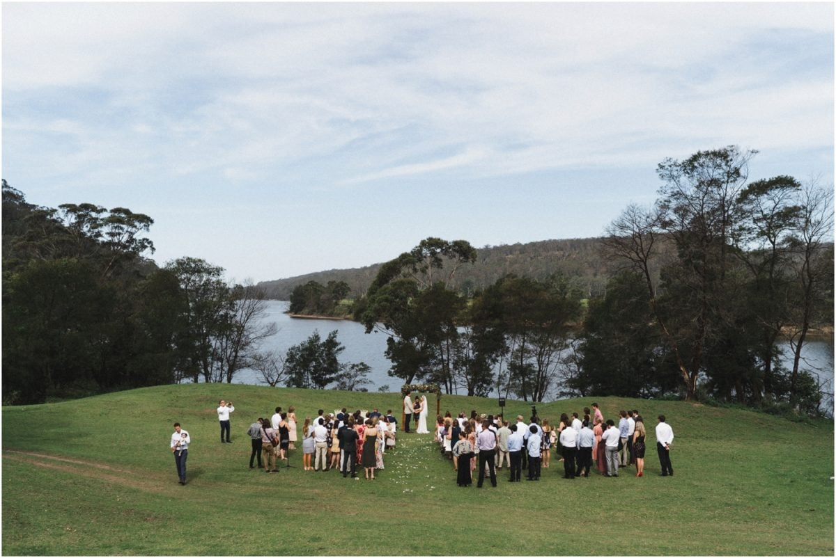A photo of a Bundanon Trust Riversdale wedding ceremony, take from high on a hill, showing the couple and their guests with a backdrop of the river