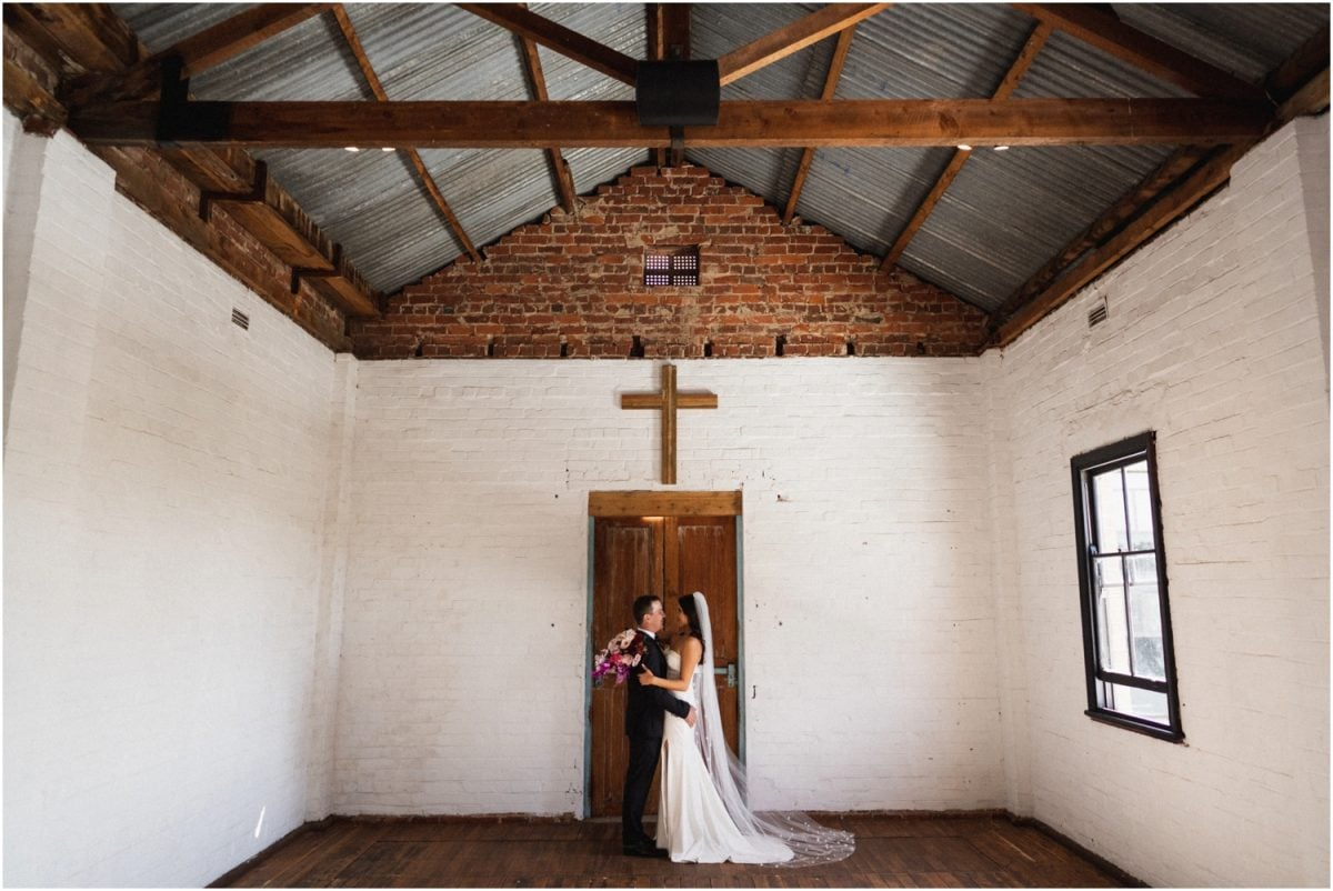 A bride and groom stand near an old door after their Uneke Warehouse wedding