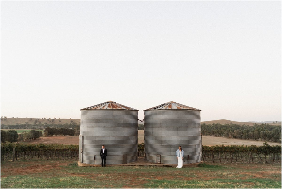 A bride and groom stand in front of two silos after their Borambola Wines wedding