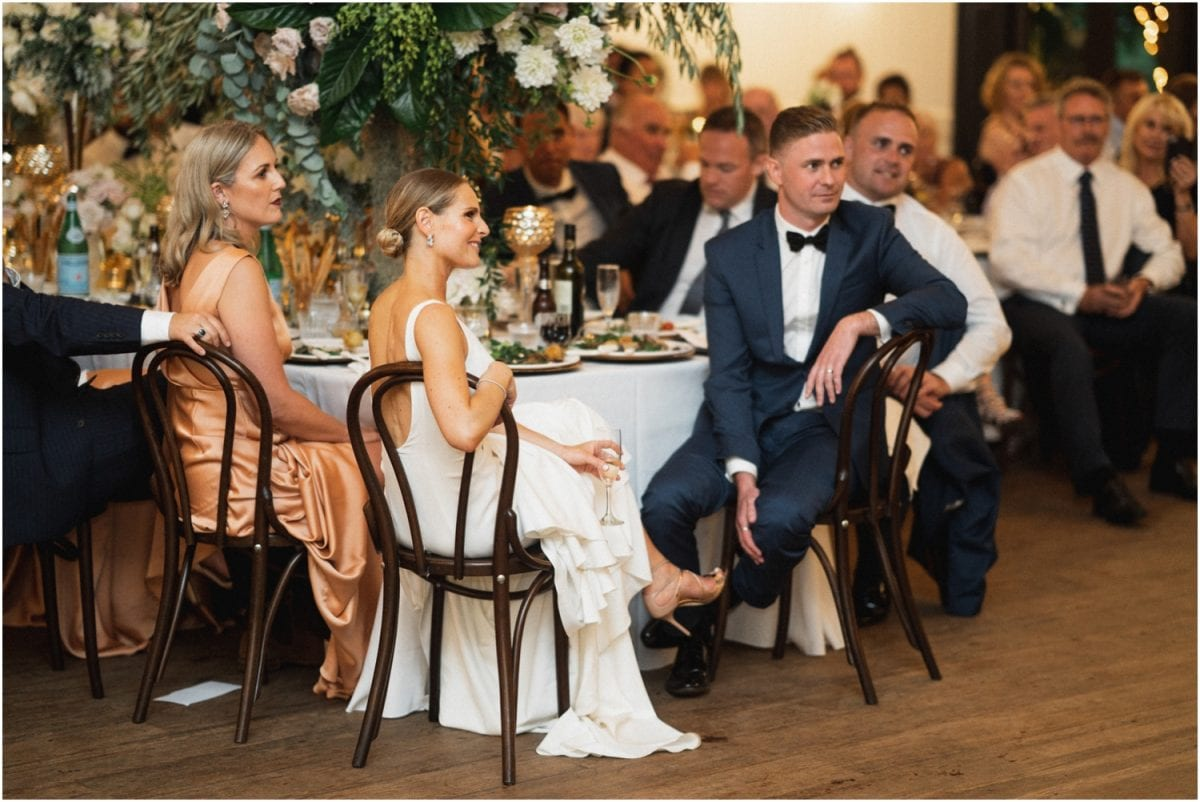 A bride and groom sit at the bridal table during their Jaspers wedding reception and listen to speeches