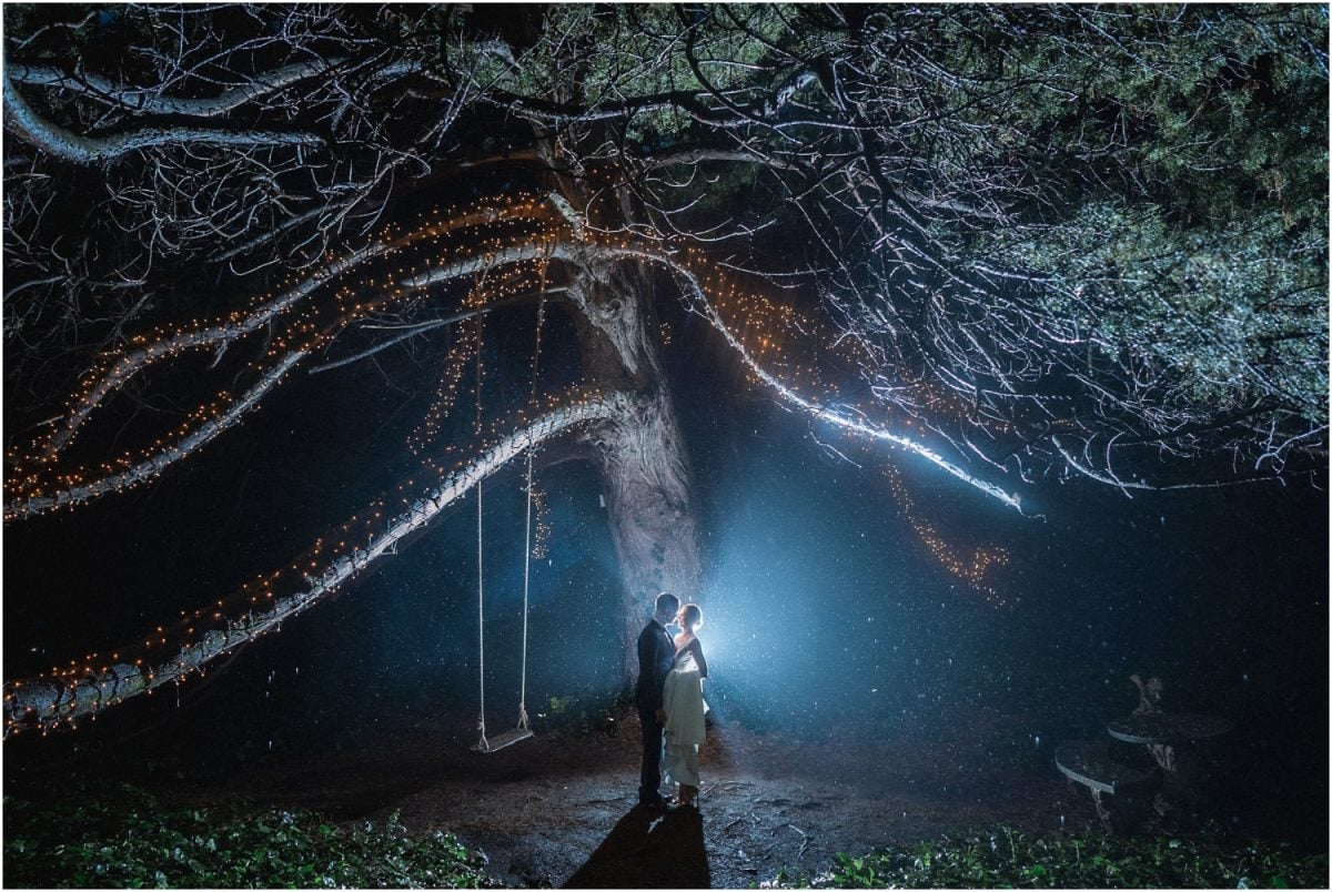 A couple in their wedding clothes stand under a tree at night at their Jaspers wedding. It's raining and the scene looks ethereal, like something out of a science fiction movie.
