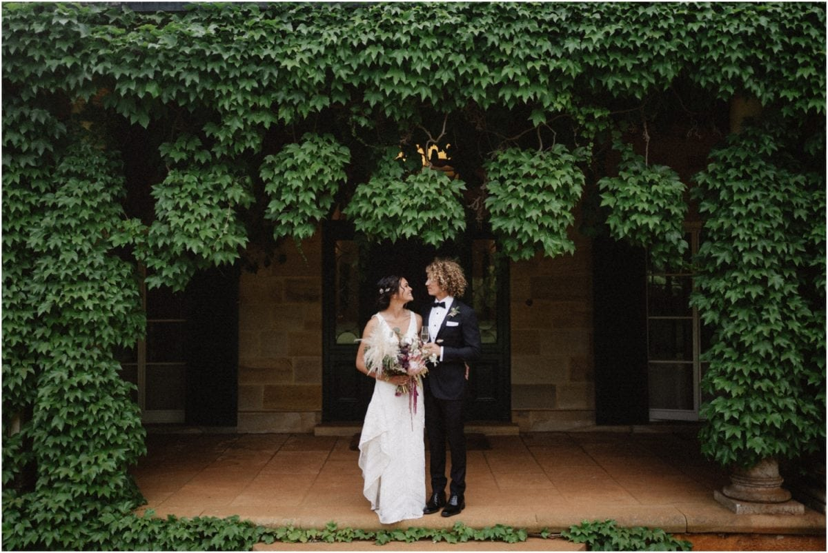 A newly married couple stand in front of the Homestead at their Bendooley Estate Book Barn wedding