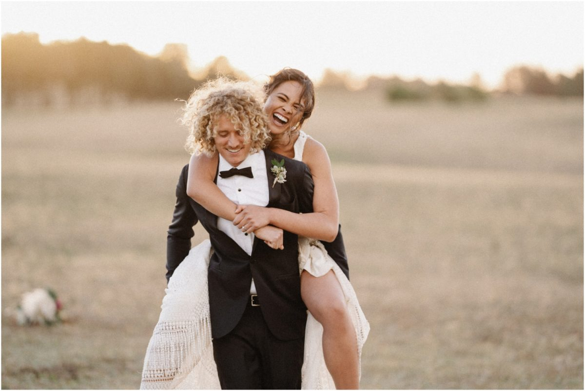 A newly married couple piggy back each other at sunset during their Bendooley Estate Book Barn wedding