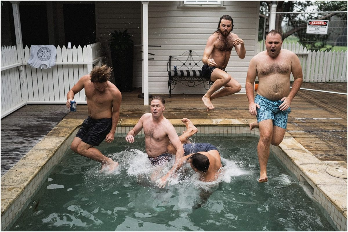 Groomsmen jump into a pool before a wedding shot by Thomas Stewart, Southern Highlands Wedding Photographers