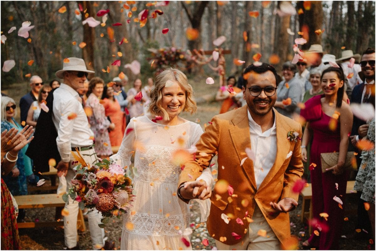 A newly married couple walk back up the aisle after their Bowral wedding ceremony, with guests throwing rose petals at them