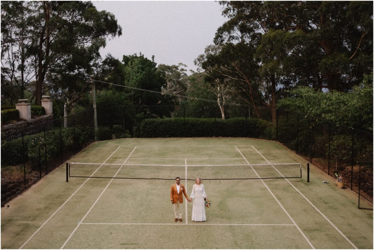 A bride and groom stand on a tennis court for a photo at their Bowral wedding