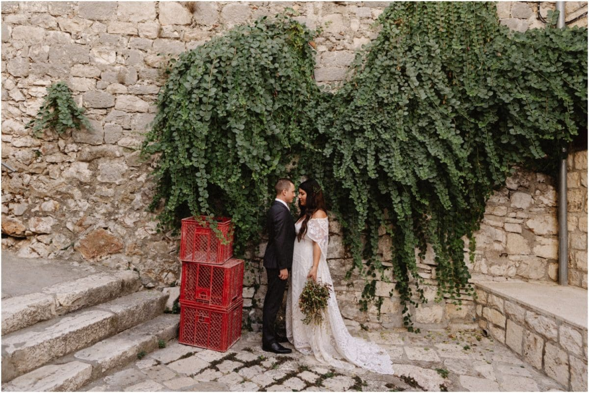 A bride and groom stand in front of a stone wall covered in ivy after their Hvar wedding in Croatia.