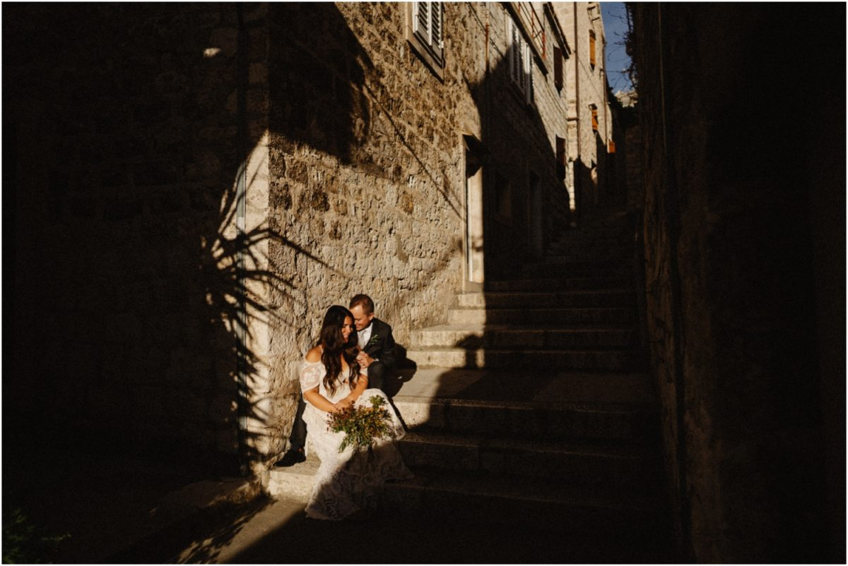 A newly married couple sit on the stairs in the old town after their Hvar wedding elopement