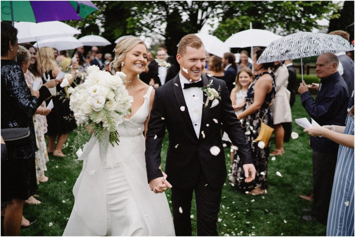A newly married couple walk back down the aisle being showered by confetti at their beautiful and rainy Centennial Vineyards Restaurant Wedding ceremony in Bowral