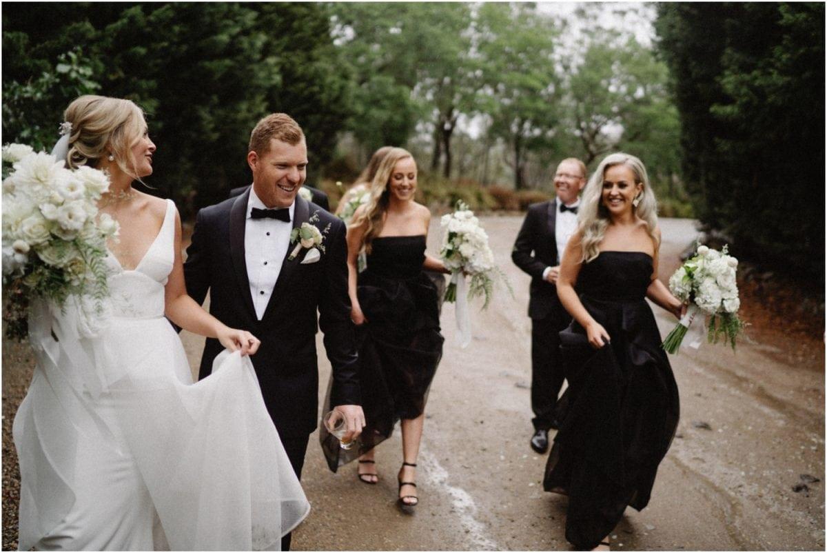 A bridal party walk along a wet path at a Centennial Vineyards Restaurant Wedding
